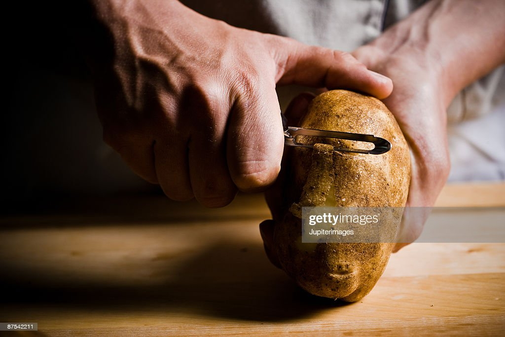 Close-up of cook peeling raw potato : Stock Photo