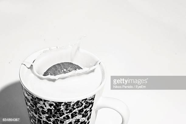 Close-Up Of Cookie In Cup Of Milk Against White Background