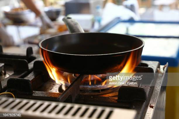 close-up of cooking pan on burning stove at restaurant - cooker stock pictures, royalty-free photos & images