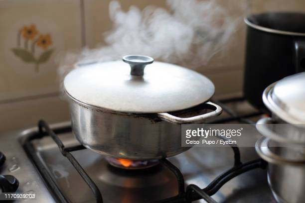 close-up of cooking pot with steam on stove top at home - burning stock pictures, royalty-free photos & images