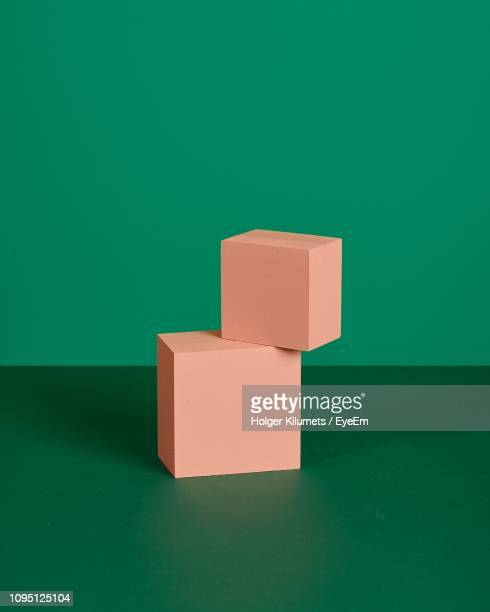 close-up of coral colored cube shapes over green background - green background stock pictures, royalty-free photos & images