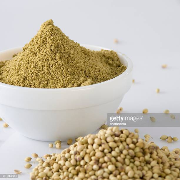 Close-up of Coriander seeds and a bowl of Coriander powder
