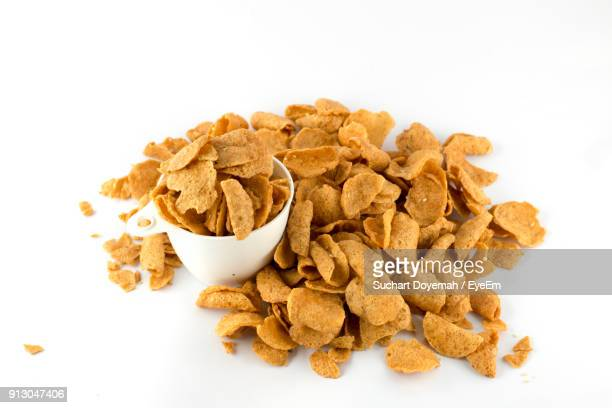 Close-Up Of Corn Flakes In Bowl Against White Background