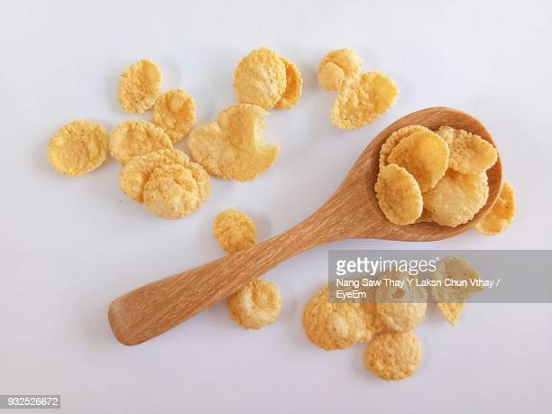 Close-Up Of Corn Flakes With Wooden Spoon On White Background