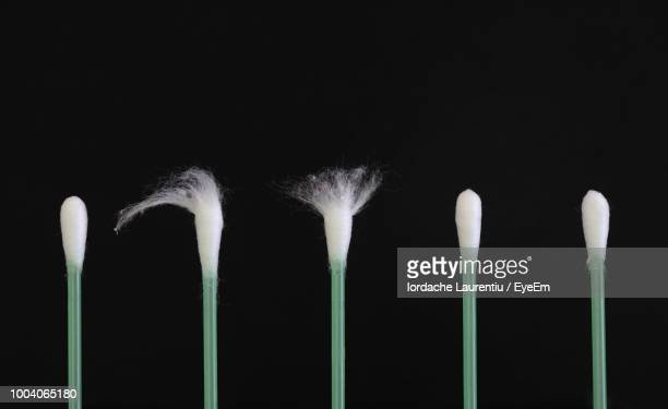 Close-Up Of Cotton Swabs Arranged Against Black Background