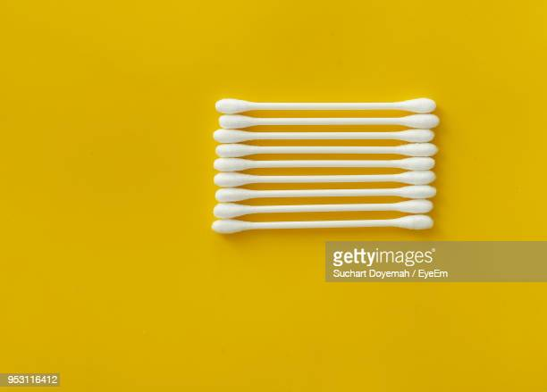 Close-Up Of Cotton Swabs Over Yellow Background