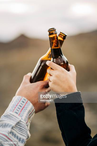 close-up of couple clinking beer bottles - honour stock pictures, royalty-free photos & images