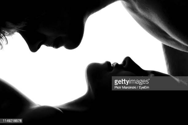 close-up of couple cuddling against white background - erotiek stockfoto's en -beelden