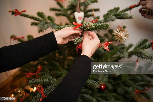 Close-up of couple decorating a Christmas tree