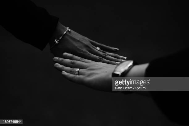 close-up of couple hands against black background - marriage stock pictures, royalty-free photos & images