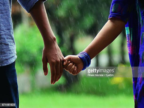 Close-Up Of Couple Holding Hand In Rain