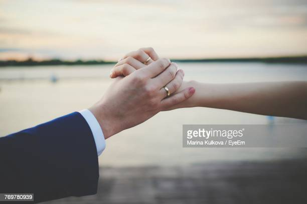 Close-Up Of Couple Holding Hands Against Sea