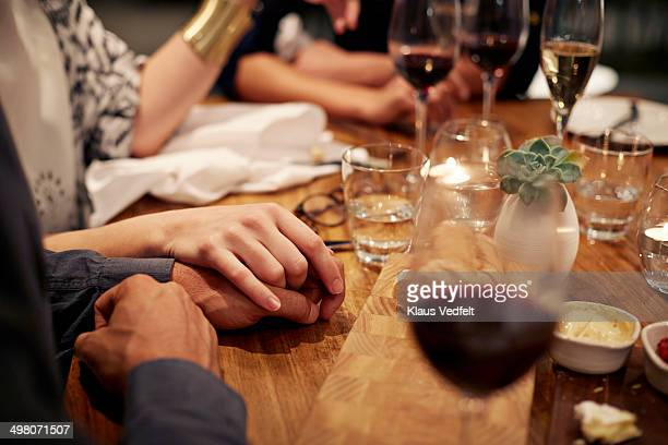 Close-up of couple holding hands at dinner table