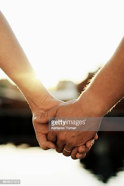 Close-up of couple holding hands at lake