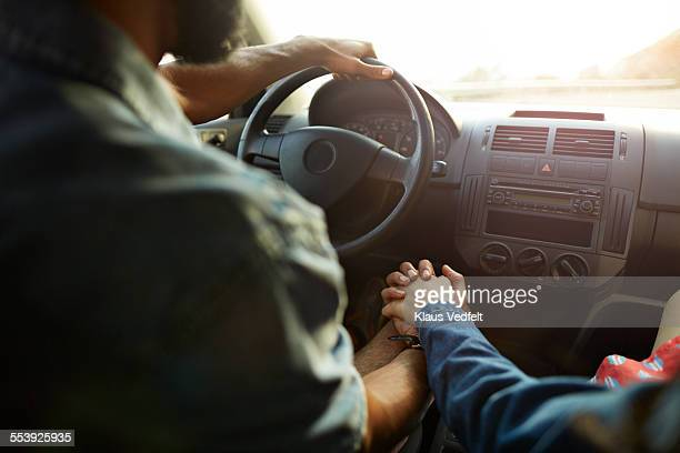 Close-up of couple holding hands inside car