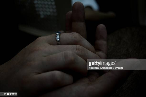 close-up of couple holding hands - man holding engagement ring stock photos and pictures