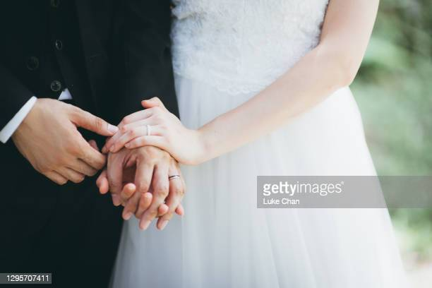 close-up of couple holding hands - wedding stock pictures, royalty-free photos & images