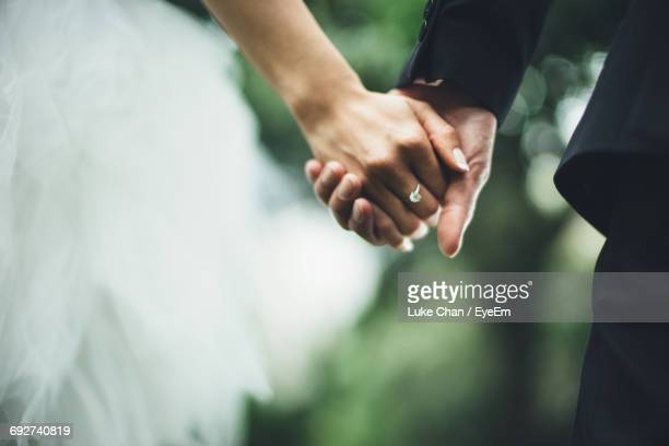 close-up of couple holding hands - trouwen stockfoto's en -beelden