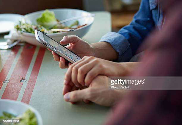 Close-up of couple holding hands & using phone