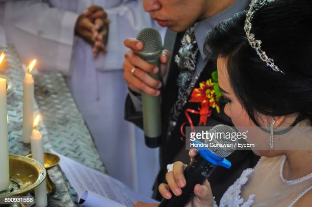 Close-Up Of Couple Holding Microphone In Church During Wedding