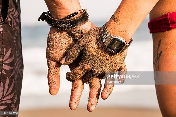 Close-up of couple holding sandy hands