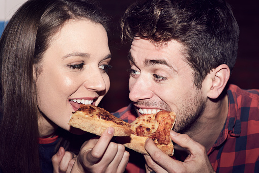Close-up of couple sharing a pizza - gettyimageskorea