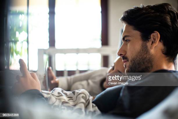 Close-up of couple using smart phones while lying on bed at home