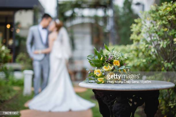 Close-Up Of Couple With Bouquet On Table