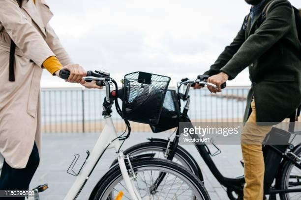 Close-up of couple with e-bikes on beach promenade