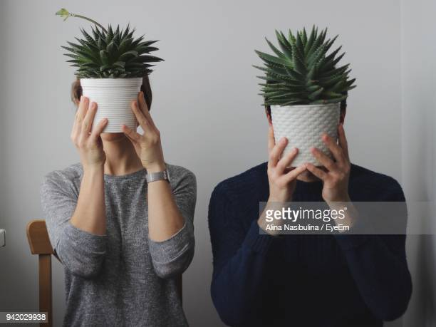 Close-Up Of Couple With Potted Plants Against Wall
