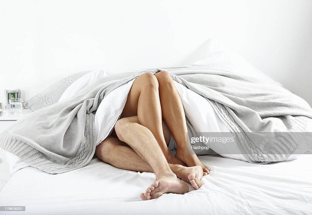 Close-up of couple's legs in bed together : Stockfoto