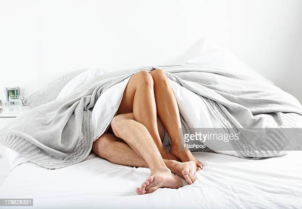 close-up of couple's legs in bed together - couple lit photos et images de collection