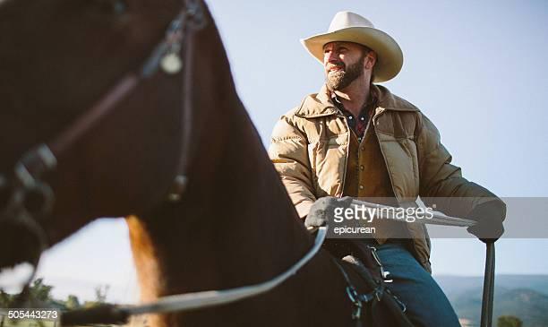 Close-up  of cowboy riding horseback with mountains behind