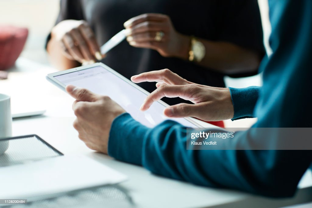 Close-up of co-workers standing at desk with laptop and talking : Stock Photo