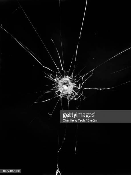 close-up of cracked glass window against black background - shattered glass stock pictures, royalty-free photos & images