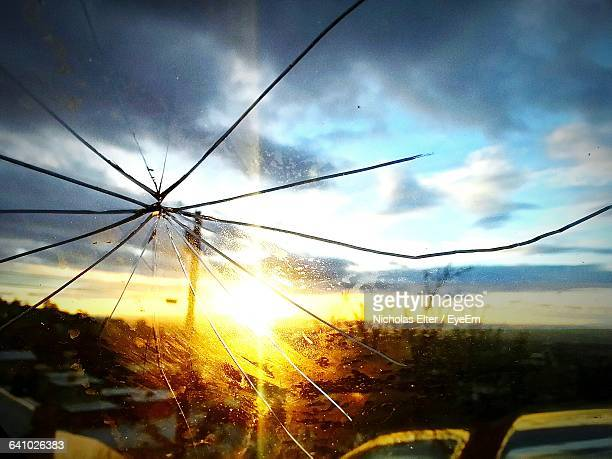 Close-Up Of Cracked Windshield Of Car Against Sky During Sunset