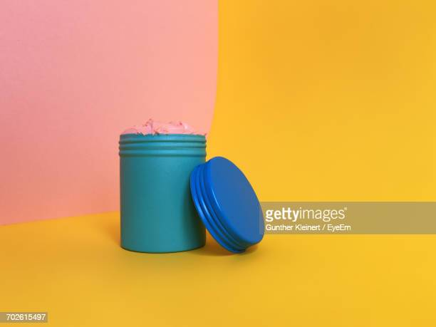 Close-Up Of Cream In Metal Jar On Colored Background