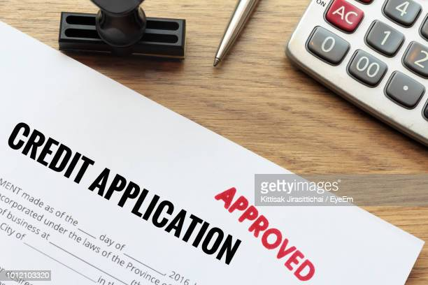 close-up of credit application form by calculator on table - application form stock pictures, royalty-free photos & images