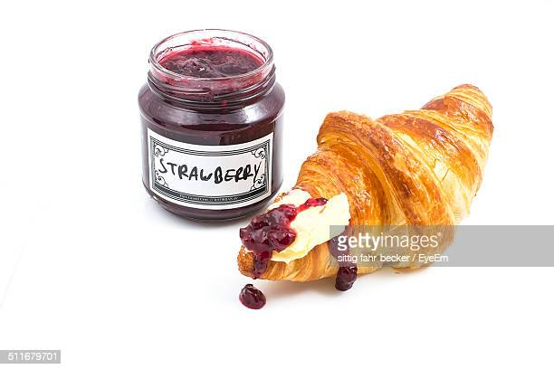 Close-up of croissant and strawberry jam over white background