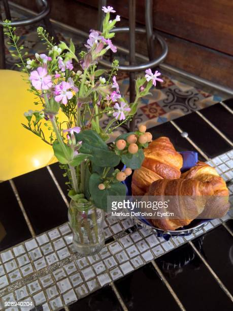 Close-Up Of Croissant By Vase On Table