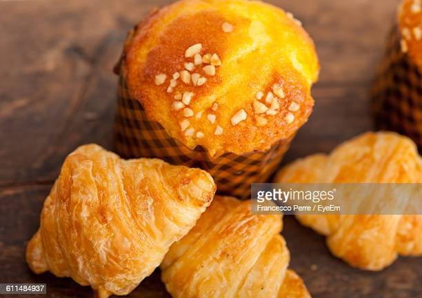 Close-Up Of Croissants With Cup Cake On Table