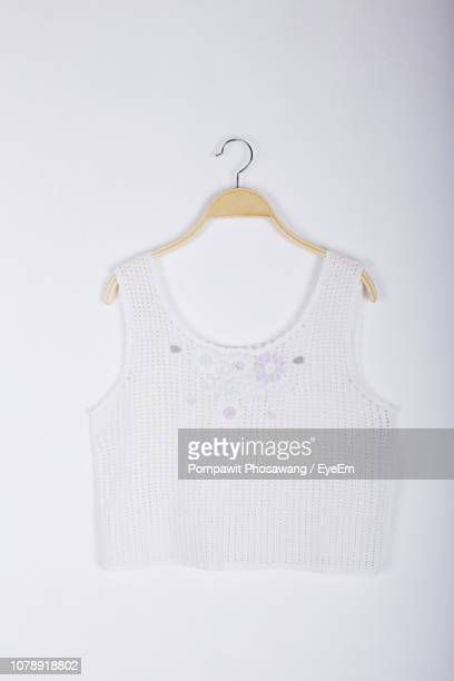 close-up of crop top hanging over white background - crop top stock pictures, royalty-free photos & images