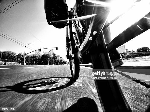 close-up of cropped bicycle moving on road - endurance stock pictures, royalty-free photos & images