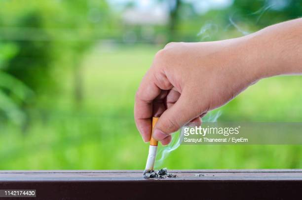 close-up of cropped hand dousing cigarette on table - extinguishing stock pictures, royalty-free photos & images