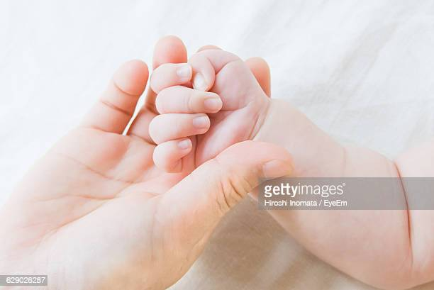 Close-Up Of Cropped Hand Holding Baby
