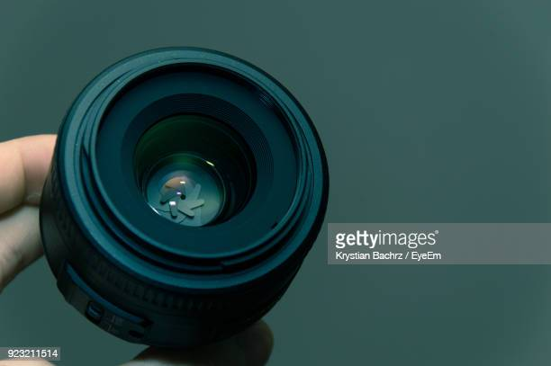 close-up of cropped hand holding camera lens against green background - lens optical instrument stock photos and pictures