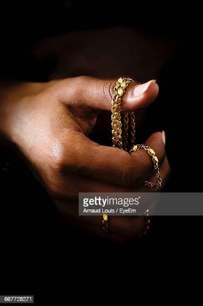close-up of cropped hand holding gold necklace - necklace stock pictures, royalty-free photos & images