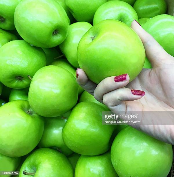 Close-Up Of Cropped Hand Holding Granny Smith Apple At Market Stall