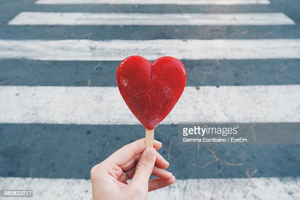 Close-up Of Cropped Hand Holding Heart Shaped Ice Cream
