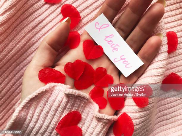close-up of cropped hand holding heart shapes and paper with i love you text - i love you photos et images de collection
